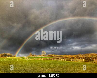Rainbow and storm clouds over pasture fields, Kingsdon, Somerset, UK - Stock Image