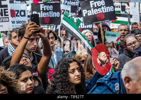 London, UK. 11th May 2019. A woman holds up a large key in the colours of the Palestinian flag in the crowd before housands march from the BBC to a rally in Whitehall a few days before Nakba day showing solidarity with the Palestinian people and opposing continued Israel violation of international law and human rights. The protest called for an end to Israeli oppression and the siege of Gaza and for a just peace that recognises Palestinian rights including the right of return. It urged everyone to boycott and divest from Israel and donate to medical aid for Palestine. Peter Marshall/Alamy Live - Stock Image