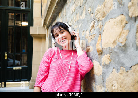 Happy beautiful girl in pink sweater listening to music in white headphones leaning in a street wall. - Stock Image