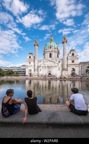 People sitting beside the pond at Karlskirche (St Charles Church), a baroque Roman Catholic church and local landmark, Vienna, Austria. - Stock Image