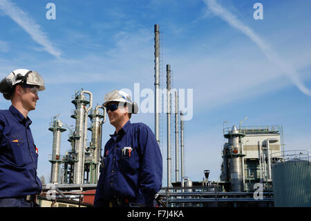 oil workers in front of refinery - Stock Image