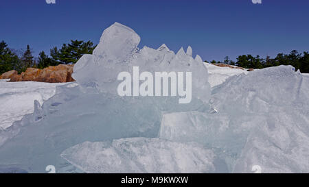Big ice formation piled up along the rocky shore of Georgian Bay, Lake Huron, Canada - Stock Image