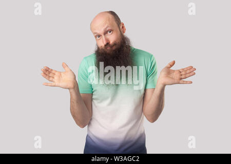 I don't know. Portrait of puzzled or confused middle aged bald man with long beard standing with raised arms and looking at camera with doubtful face. - Stock Image