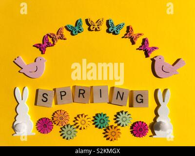 Spring, in wooden letters with bunnies, flowers birds and butterflies - Stock Image