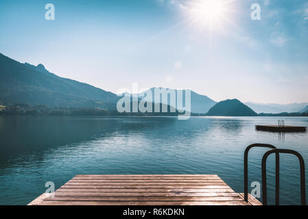 Beautiful sunrise above the alpine valley. Wooden pier on mountain lake in Alps - Stock Image