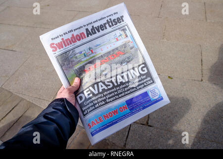 Swindon, Wiltshire, UK. 19th February, 2019. On the day that Honda has confirmed that they will be closing their car factory in the town a man is pictured holding the local Swindon newspaper which has news of Honda's closure on it's front page. Swindon was one of the first areas to declare a Leave result in the 2016 EU referendum. Many in the local community are worried that the job losses at Honda will have a catastrophic impact on the town. Credit: Lynchpics/Alamy Live News - Stock Image