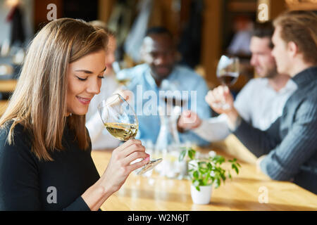Young woman is drinking a glass of wine on a wine tasting together with friends - Stock Image