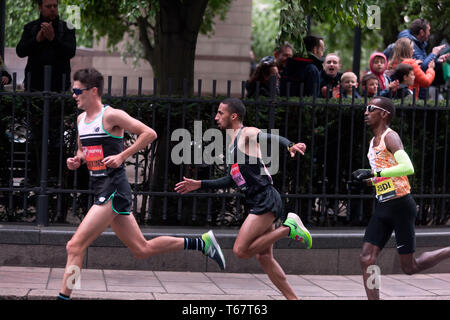 Callum Hawkins (GBR), Yassine Rachik (ITA) and Bashir Abdi (BEL), battling it out around Canary Wharf, during the 2019 London Marathon. They went on to finish 10th, 9th and 7th respectively  in the Men's elite race. - Stock Image