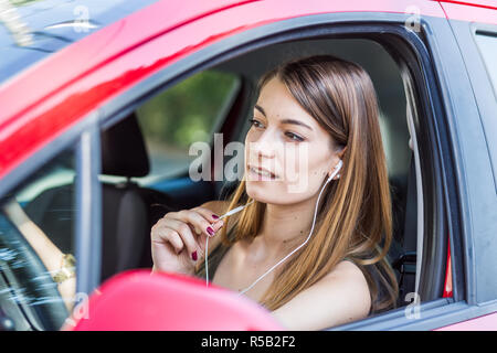 Woman using a hands-free kit while driving. - Stock Image