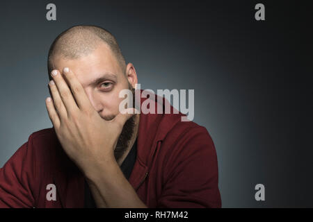 Portrait man covering face with hand - Stock Image