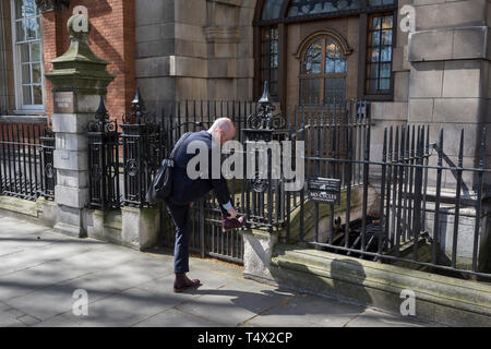 A male pedestrian attends to a loose shoe lace, on 10th April 2019, in Westminster, London, UK - Stock Image