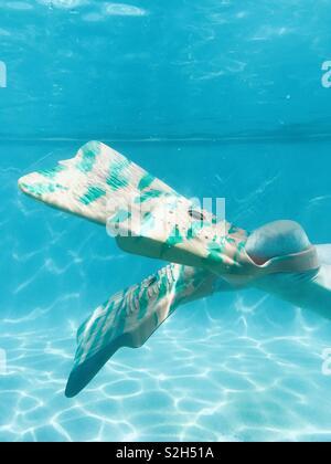 A women swimming underwater wearing swim fins. Fiji. - Stock Image