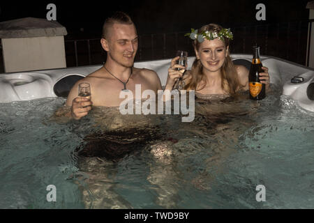 Couple relaxing in hot tub after Wedding, Jennycliff, Plymouth, Devon, UK - Stock Image