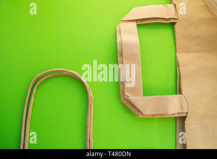 Zero waste, plastic free recycled production bag into paper bag, environmental protection concept, top view, green background, flat lay, copy space - Stock Image