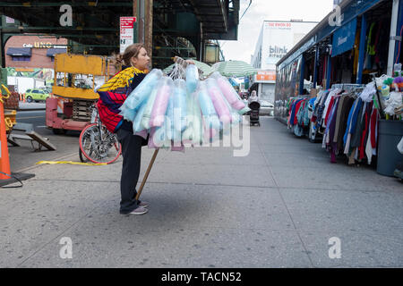A Latin American woman selling bags of cotton candy under the elevated subway in Jackson Heights, Queens, New York City. - Stock Image