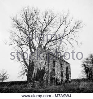 Disused and derelict  storehouse building on the Monmouthshire and Brecon Canal near Llanfrynach, Powys, Wales, - Stock Image