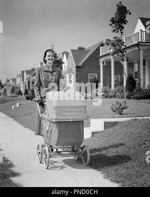1950s SMILING WOMAN MOTHER WALKING PUSHING BABY CARRIAGE ALONG SUBURBAN SIDEWALK - b6955 HAR001 HARS ACTIVITY HAPPINESS PHYSICAL STRENGTHENING CHEERFUL SELF ESTEEM ALONG PRIDE SMILES MENTAL HEALTH FLEXIBILITY JOYFUL MUSCLES STYLISH BABY CARRIAGES MID-ADULT MID-ADULT WOMAN MOMS RELAXATION BABY CARRIAGE BLACK AND WHITE CAUCASIAN ETHNICITY HAR001 OLD FASHIONED PRAMS - Stock Image