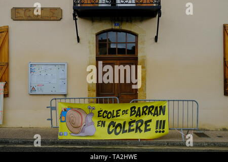 Banner and barricades in front of school door to protest the closing ofone class out four of the village school, in Barran, France, May 2019 - Stock Image