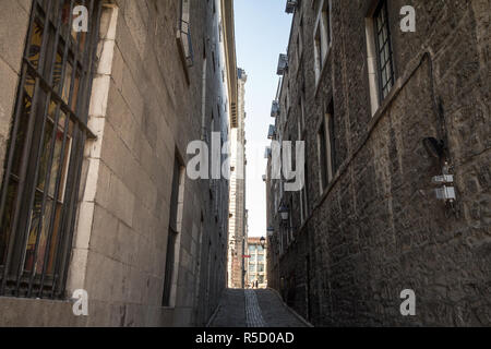 MONTREAL, CANADA - NOVEMBER 4, 2018: Narrow street of the Old Montreal, or Vieux Montreal, bordered with old stone buildings. It is the historic distr - Stock Image