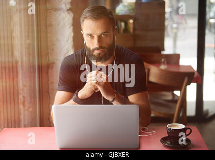 Young Bearded Businessman Wearing Black Tshirt Working Laptop Urban Cafe.Man Sitting Wood Table Cup Coffee Listening - Stock Image