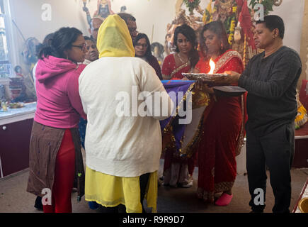 A hindu congregation in performs the Arti ritual of offering light and flames to the deities. In Queens, New York City. - Stock Image
