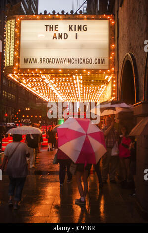 Chicago, United States. 14th Jun,  2017. A bright pink and white umbrella lightens up the atmosphere as a mass of - Stock Image