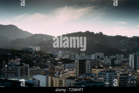 Cityscape of high rises with a favela in background, Rio de Janeiro, Brazil - grain added for effect - Stock Image