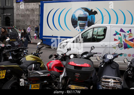 The design on the side of an HGV for the rehearsal studio company 'Fly By Nite' and and a courier van in Great Marlborough Street, on 5th March 2019, in London, England. - Stock Image