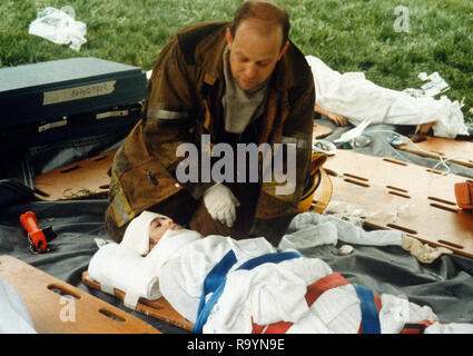 Fiirefighter consoles an injured child - Stock Image