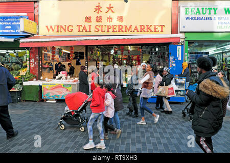 Shoppers walking outside Wing Tai Chinese Supermarket store & Brixton street market Electric Avenue Brixton South London SW9 England UK KATHY DEWITT - Stock Image