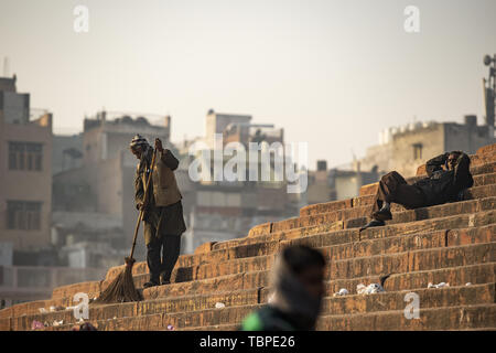 An Indian worker is sweeping the courtyard of the Jama Masjid in New Delhi. Jama Masjid is one of the largest mosque in India. - Stock Image