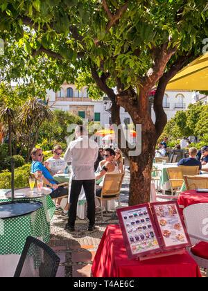 Alfresco dining, waiter taking order with illustrated menu in foreground.  Marbella Orange Square - Plaza de los Naranjos,  Old Town Marbella Spain - Stock Image