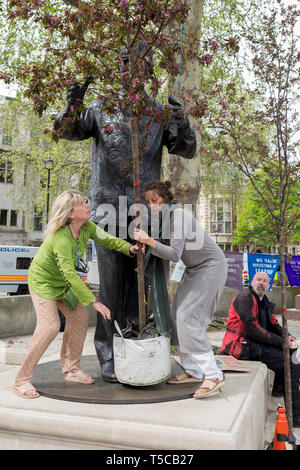 Women campaigners position a large potted tree at the feet of Nelson Mandela's statue in Parliament Square during the week-long protest by climate change activists with Extinction Rebellion's campaign to block road junctions and bridges around the capital, on 23rd April 2019, in London England. - Stock Image