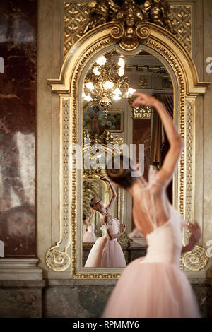 Beautiful ballerina in pink dress dancing in front of the mirror on background of her reflection and luxurious interior. - Stock Image