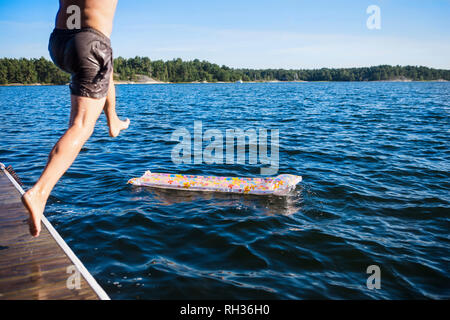 Man jumping into water - Stock Image