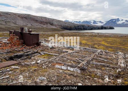 The rusting remains of a stove remain in position above the wooden foundations of an abandoned hut at New London - Stock Image