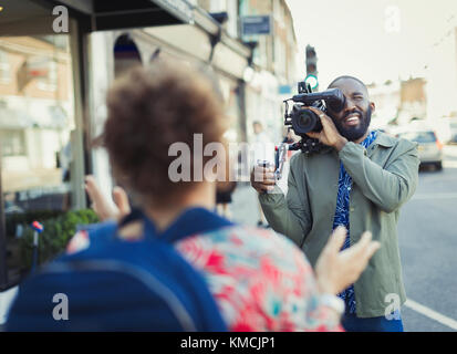Young man with video camera videoing woman on street - Stock Image
