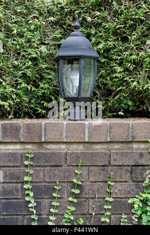 Outdoor decorative electric metal lantern on a brick graden wall - Stock Image