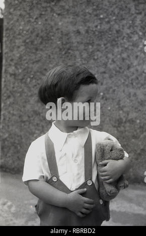 1950s, historical, 'cheeky chappy'...a young boy with his teddy bear and wearing shorts with braces, looking the other way and smiles. - Stock Image