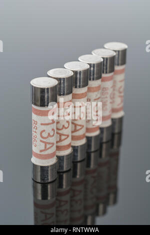 Domestic appliance electrical 13 Amp fuses (Ceramic Cartridge type) on reflective black background. Metaphor electrical safety. 25mm L x 6.3mm D - Stock Image