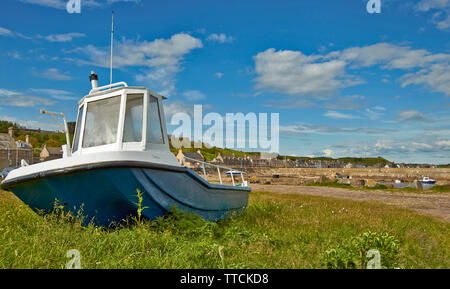 PORTGORDON MORAY SCOTLAND OLD FISHING BOAT THE HARBOUR AND VILLAGE HOUSES - Stock Image
