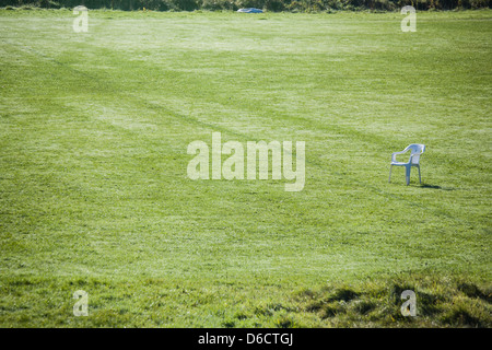 Empty playing field with one white plastic chair to the right. Space,solitude,loneliness,peace,quiet,sport - Stock Image