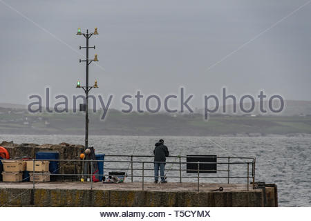 Mousehole, Cornwall, UK. 24th Apr, 2019. UK Weather. Still mild, but overcast and windy start to the day for south west Cornwall. A fisherman seen here casting his line off the wall of Mousehole harbour. Credit: Simon Maycock/Alamy Live News - Stock Image