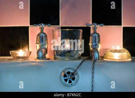 traditional bath and chrome taps lit by candles - Stock Image