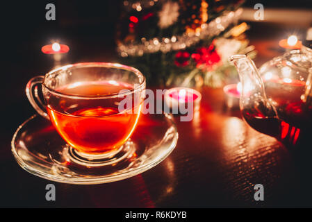 Tea cup and tea pot near christmas tree on the table - Stock Image