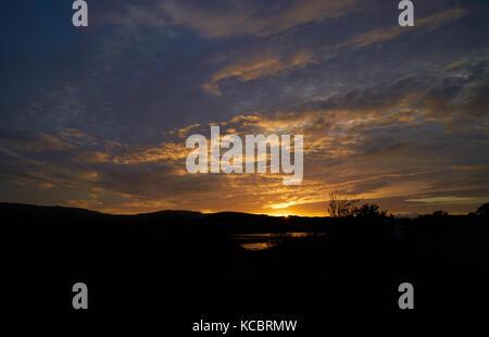 The sun setting over Loch Dunvegan on the Isle of Skye, Scottish Highlands, Scotland, UK. - Stock Image