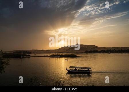 Tourist boats sailing on Nile River at sunset, Aswan, Egypt - Stock Image