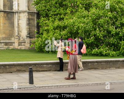 Oriental people taking photos on mobile phones Cambridge 2019 - Stock Image
