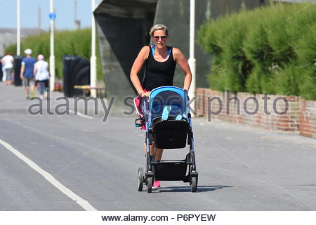 Littlehampton, UK. Monday 2nd July 2018. A woman runs on the promenade with a pushchair on another very warm and humid morning in Littlehampton, on the South Coast. Credit: Geoff Smith / Alamy Live News. - Stock Image