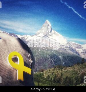 Catalan tourist with a yellow ribbon pinned in her cap in front of a view of Matterhorn, Zermatt, Wallis or Valais, Switzerland. Symbol of solidarity with the jailed pro-independence catalan leaders. - Stock Image